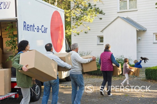 Germany, Bavaria, Grobenzell, Family carrying cardboard box for moving house : Stock Photo