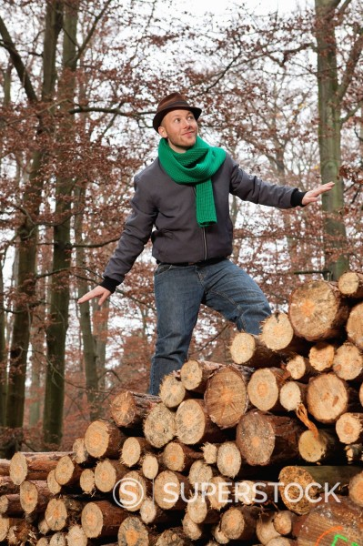 Stock Photo: 1815R-94390 Germany, Berlin, Wandlitz, Young man standing on stack of wood