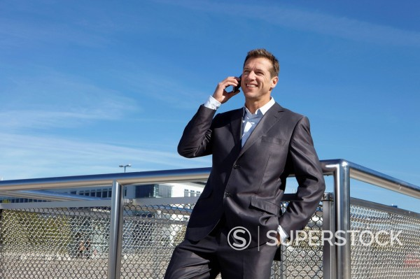 Germany, Bavaria, Munich,Businessman talking on cell phone, smiling : Stock Photo