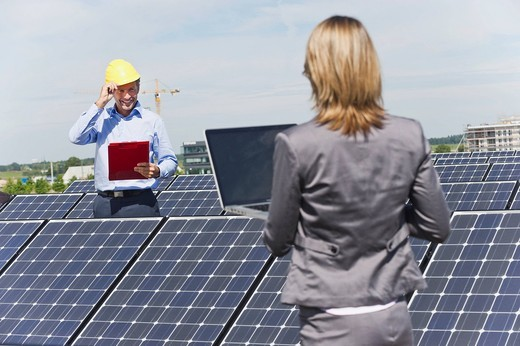 Germany, Munich, Engineers with laptop and discussing in solar plant : Stock Photo