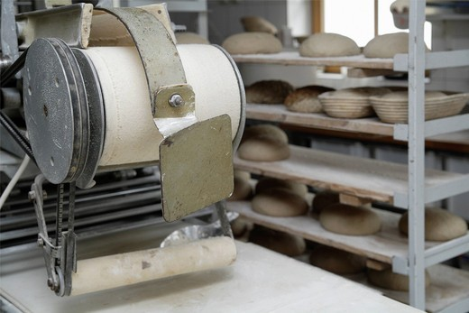 Germany, Upper Bavaria, Egling, Roll out machine in wood stove bakery : Stock Photo