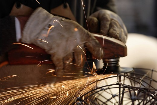 Germany, Upper Bavaria, Munich, Schaeftlarn, Sculptor abrasive cutting at work : Stock Photo