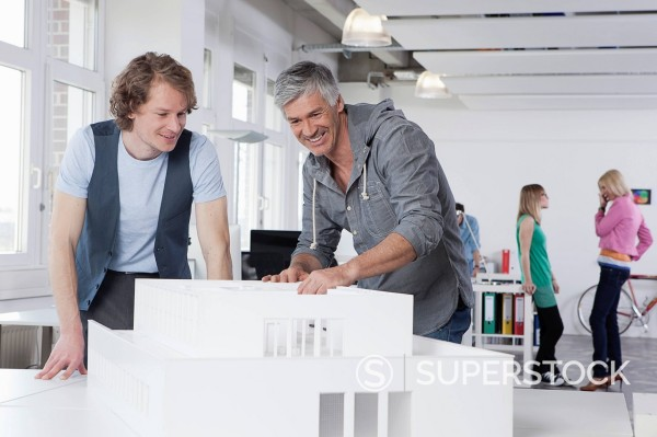 Germany, Bavaria, Munich, Men watching architectural model in office, colleagues talking in background : Stock Photo