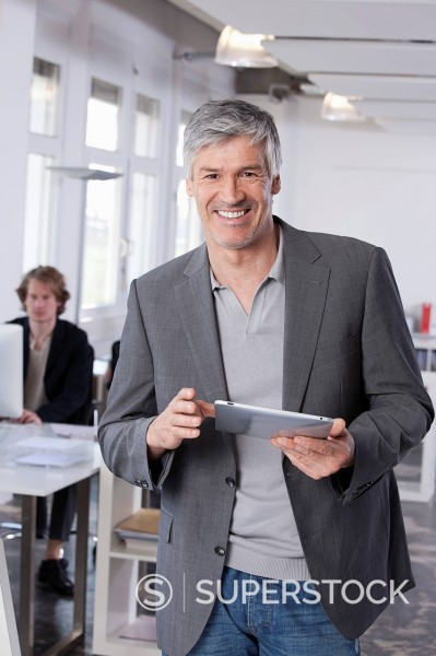 Germany, Bavaria, Munich, Mature man using digital tablet, colleague working in background : Stock Photo