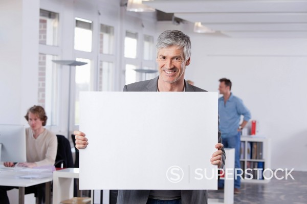 Stock Photo: 1815R-96750 Germany, Bavaria, Munich, Mature man holding placard in office
