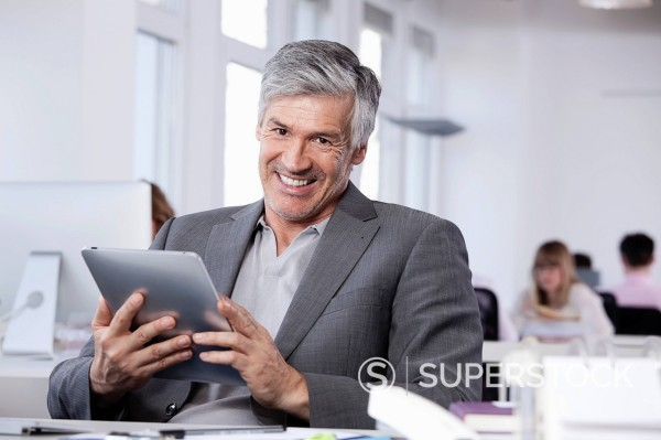 Germany, Bavaria, Munich, Mature man using digital tablet, colleagues working in background : Stock Photo
