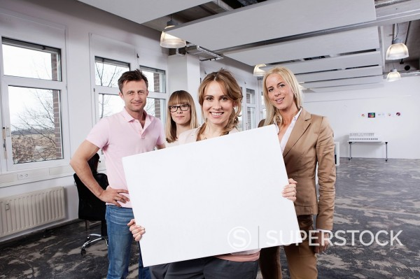 Germany, Bavaria, Munich, Young woman holding placard with colleagues in office : Stock Photo