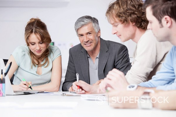 Stock Photo: 1815R-96793 Germany, Bavaria, Munich, Mature man smiling, colleagues working