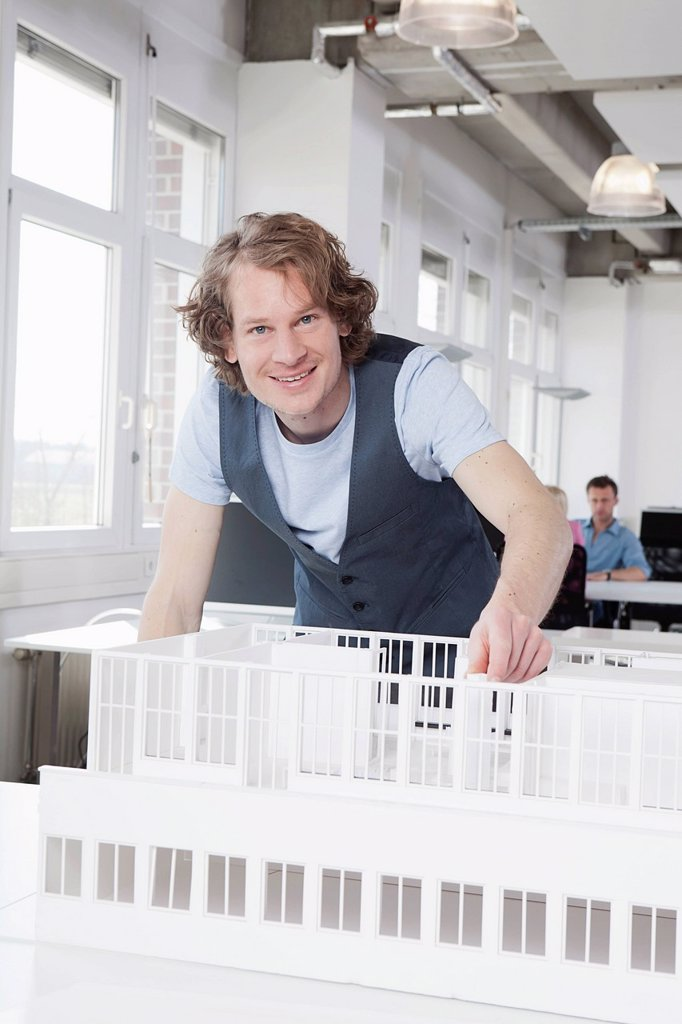 Germany, Bavaria, Munich, Architect with architectural model, colleagues working in background : Stock Photo