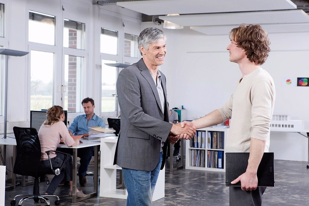Stock Photo: 1815R-97046 Germany, Bavaria, Munich, Men shaking hands while colleague working in backgorund