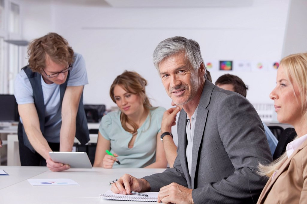 Stock Photo: 1815R-97060 Germany, Bavaria, Munich, Mature man smiling while colleagues working in background