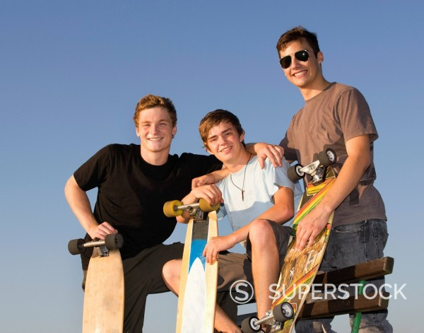 Stock Photo: 1815R-97195 Austria, Young men with skateboard, smiling, portrait