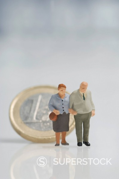 Senior couple figurines in front of euro coin : Stock Photo