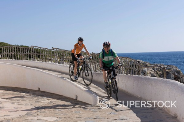 Spain, Minorca, Binibeca, Man and woman cycling by sea : Stock Photo