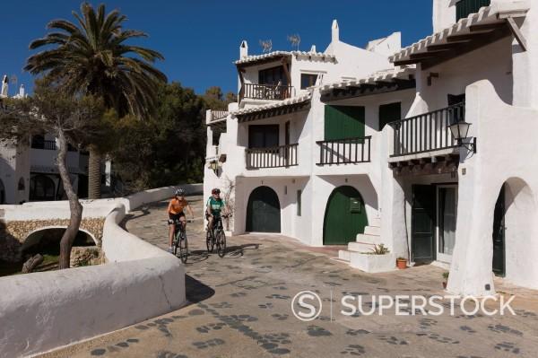 Spain, Minorca, Binibeca, Man and woman cycling through promenade : Stock Photo