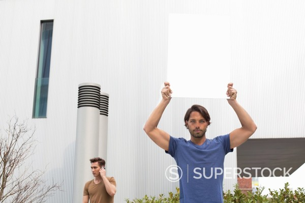 Germany, North Rhine Westphalia, Duesseldorf, Trainee with shield, man using mobile phone in background : Stock Photo