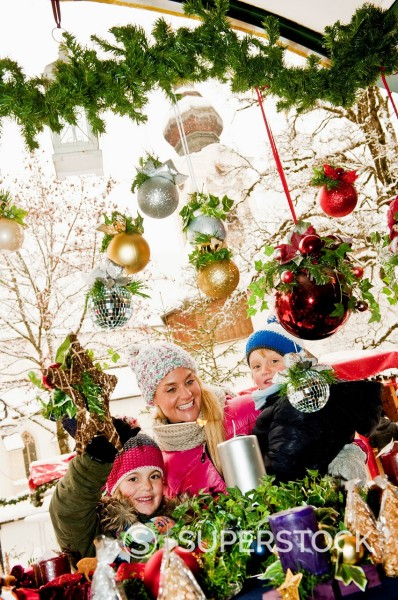 Austria, Salzburg, Mother with children at christmas market, smiling : Stock Photo