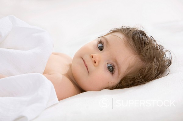 Stock Photo: 1815R-99103 Baby girl lying on back, covered with blanket, portrait