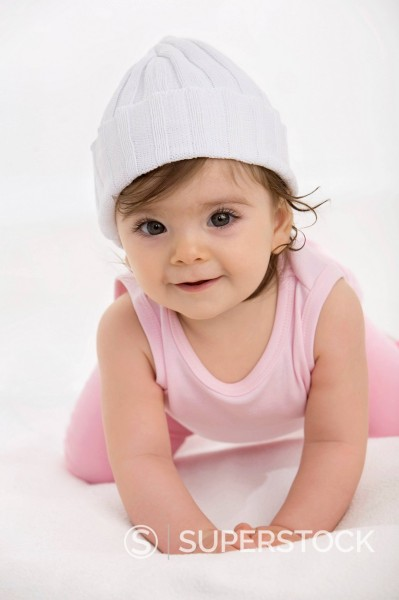 Stock Photo: 1815R-99328 Baby girl crawling on baby blanket