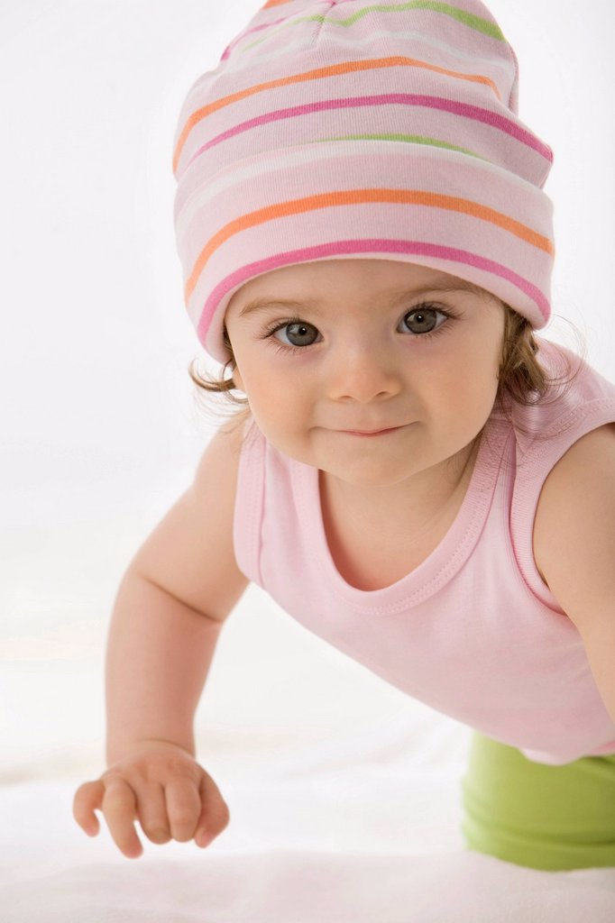 Stock Photo: 1815R-99336 Baby girl crawling on baby blanket, smiling