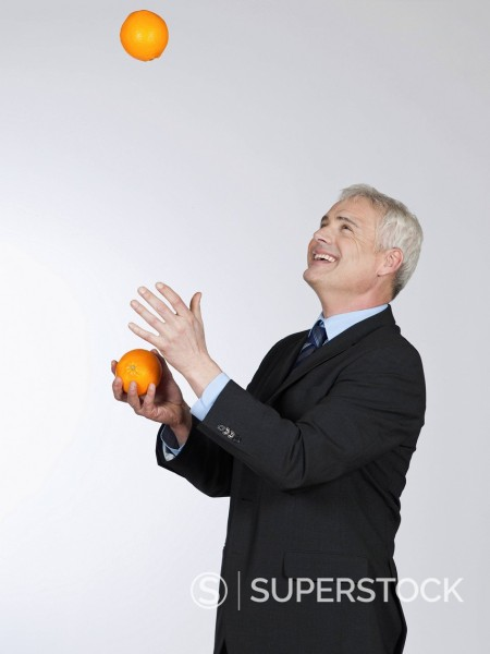 Stock Photo: 1815R-99388 Mature man juggling with oranges