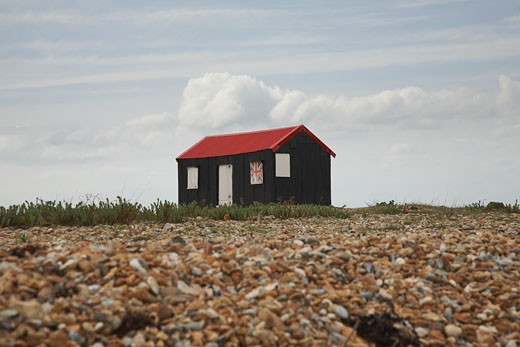 Rustic red roofed beach hut with Union Jack shutter in England : Stock Photo