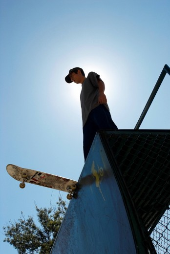 Low angle view of a young male skateboarder standing on a stunt ramp : Stock Photo