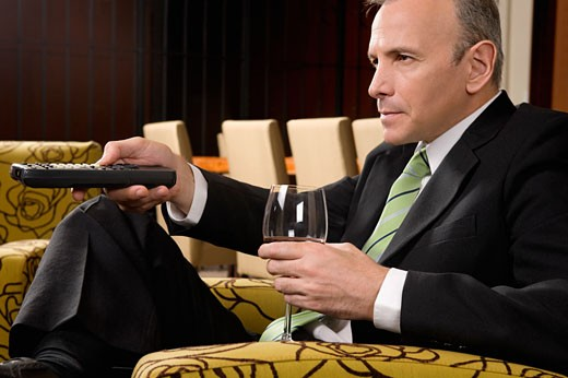 Businessman operating a remote control and holding a wine glass : Stock Photo