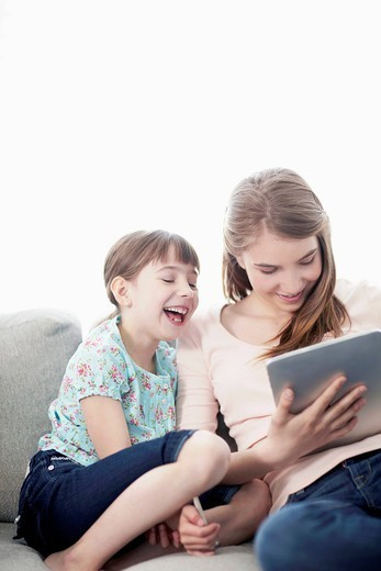 Sisters 6_7, 10_12 having fun while using digital tablet : Stock Photo