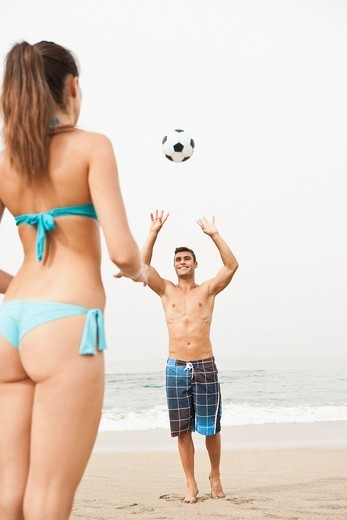 Young couple playing football on beach : Stock Photo
