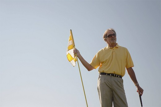 Man holding golf flag : Stock Photo