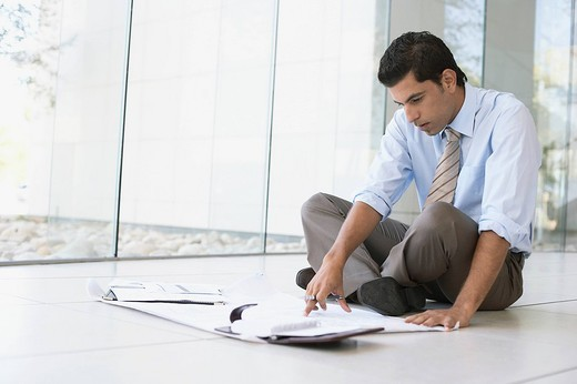 Financial advisor sitting on the floor : Stock Photo