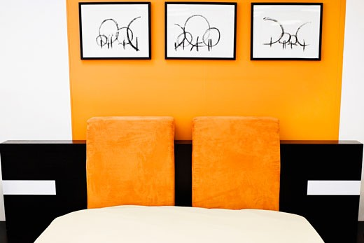 Paintings on a wall near a bed : Stock Photo