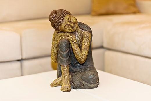 Figurine of Buddha on a table : Stock Photo