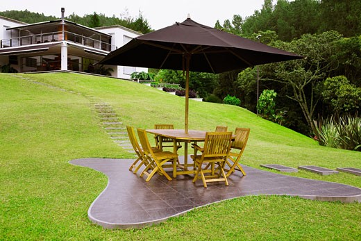 Table and chairs under a patio umbrella in a lawn : Stock Photo