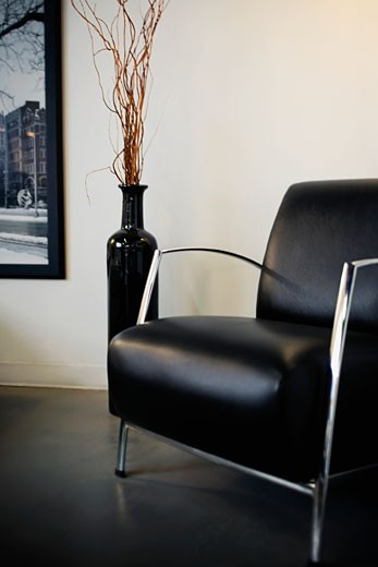 Vase beside an armchair : Stock Photo