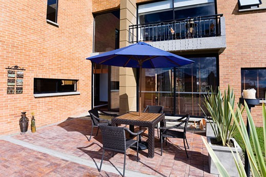 Stock Photo: 1825-2844 Chairs with a patio umbrella in the courtyard of a house