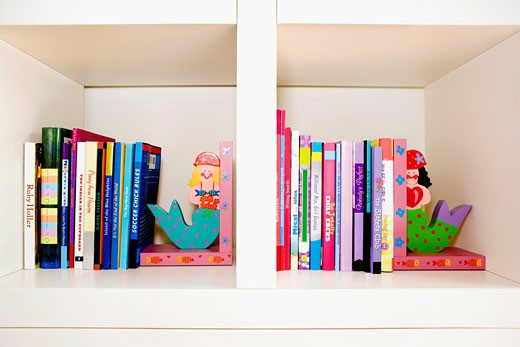 Close-up of books and toy mermaids on a shelf : Stock Photo