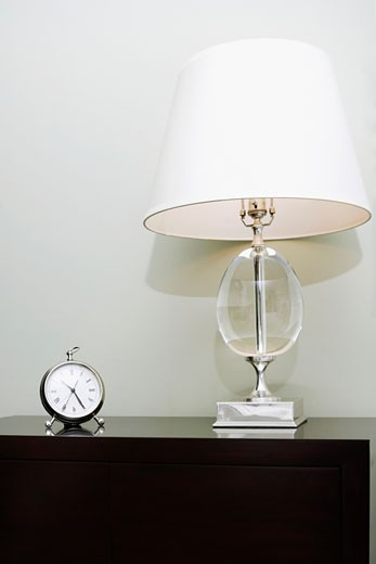 Alarm clock and a lamp on a chest : Stock Photo