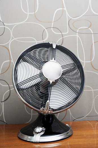 Electric fan on a sideboard : Stock Photo