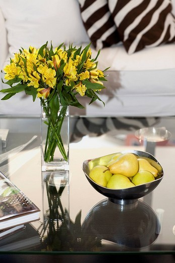 Flower vase and a bowl of artificial pears on a table : Stock Photo