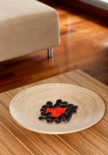 Pebbles in a wooden plate on a table : Stock Photo