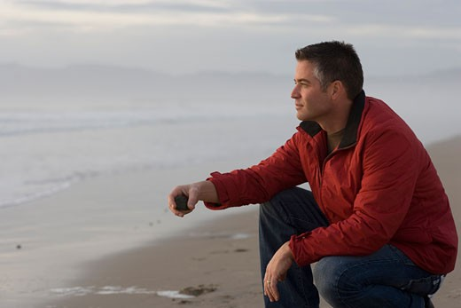 Side profile of a mid adult man holding a stone on the beach : Stock Photo