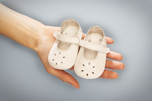 Stock Photo: 1828R-11023 Hands Holding Baby Shoes