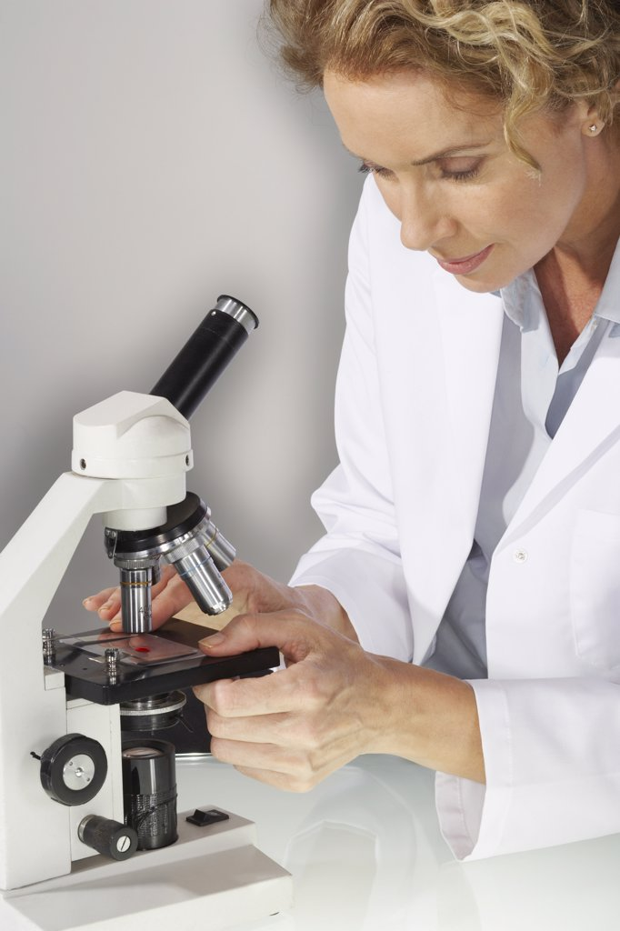 Stock Photo: 1828R-11231 Doctor Looking Into Microscope