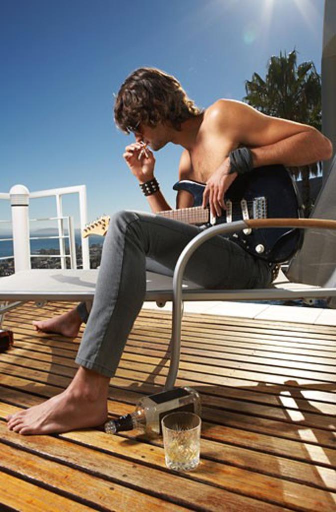 Stock Photo: 1828R-11635 Man Holding Guitar, Smoking Cigarette