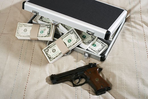 Stock Photo: 1828R-12331 Gun and Briefcase Full of Money