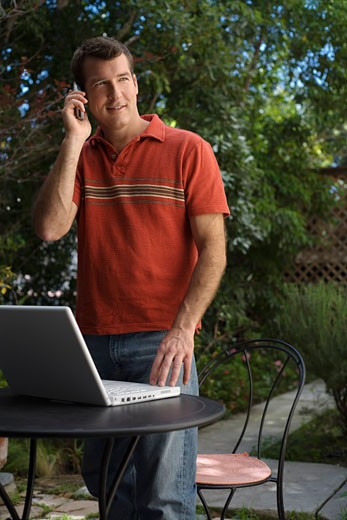 Stock Photo: 1828R-13218 Man in Backyard using Cell Phone and Computer