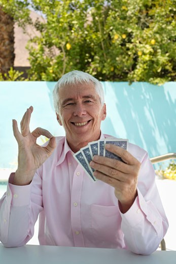 Stock Photo: 1828R-13244 Man Holding Playing Cards and Showing OK Sign