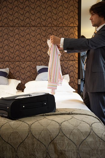 Stock Photo: 1828R-13431 Businessman Folding Shirt in Hotel Room